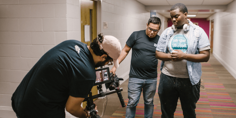 Film crew showing a young Black man how to use equipment