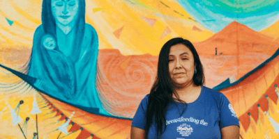 New Mexico mother stands in front of a mural