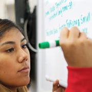 Former intern Rayes Crespin writes answers on a board in class at the University of New Mexico,