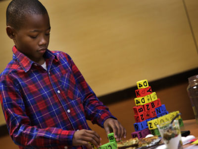 Young African American boy playing with blocks at Hope Starts Here announcement