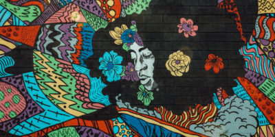 "8 Mile's newest mural entitled ""Detroit is a Black Woman."" The mural features the head of a black woman surrounded by colorful graphics and flowers"