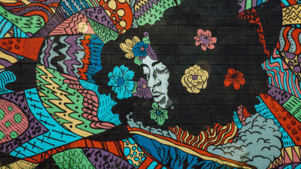 """8 Mile's newest mural entitled """"Detroit is a Black Woman."""" The mural features the head of a black woman surrounded by colorful graphics and flowers"""