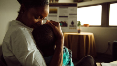 Malikah Garner holds her son and kisses his forehead while sitting in an office