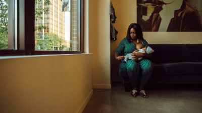 Diamond Massey breastfeeds her infant child while waiting at a hair salon