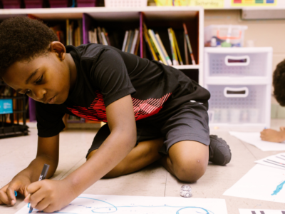 Young boys of color drawing in a classroom