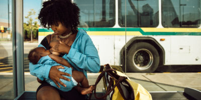 Janel Vee breastfeeds her infant daughter outside at a bus stop.
