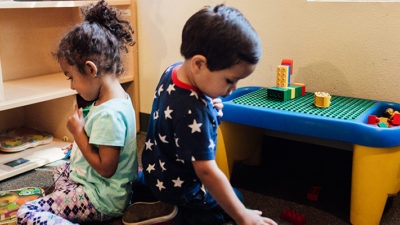 A young boy and a young girl play with toys in an early childhood education classroom