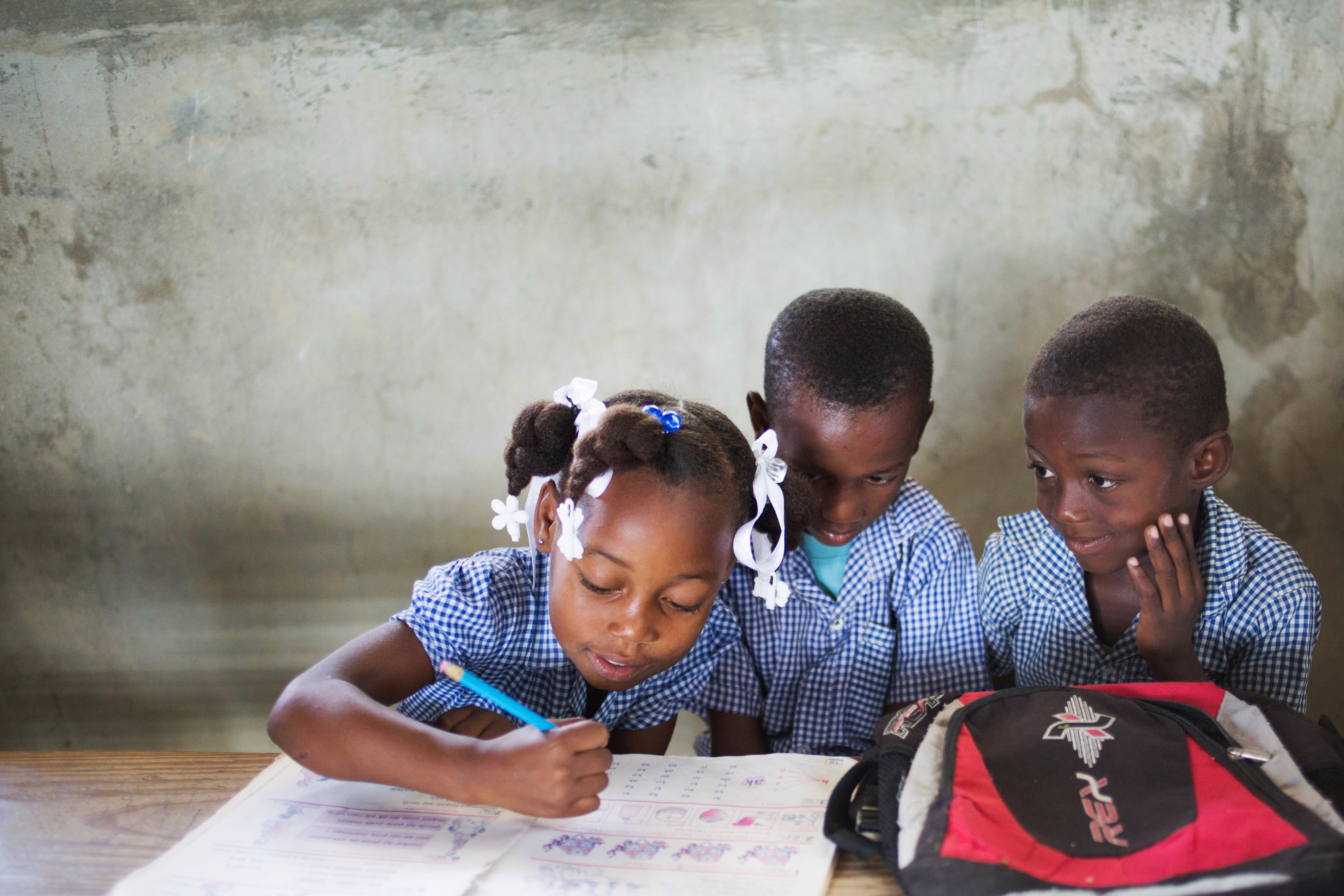 Three students in Haiti working on their assignment in a classroom.