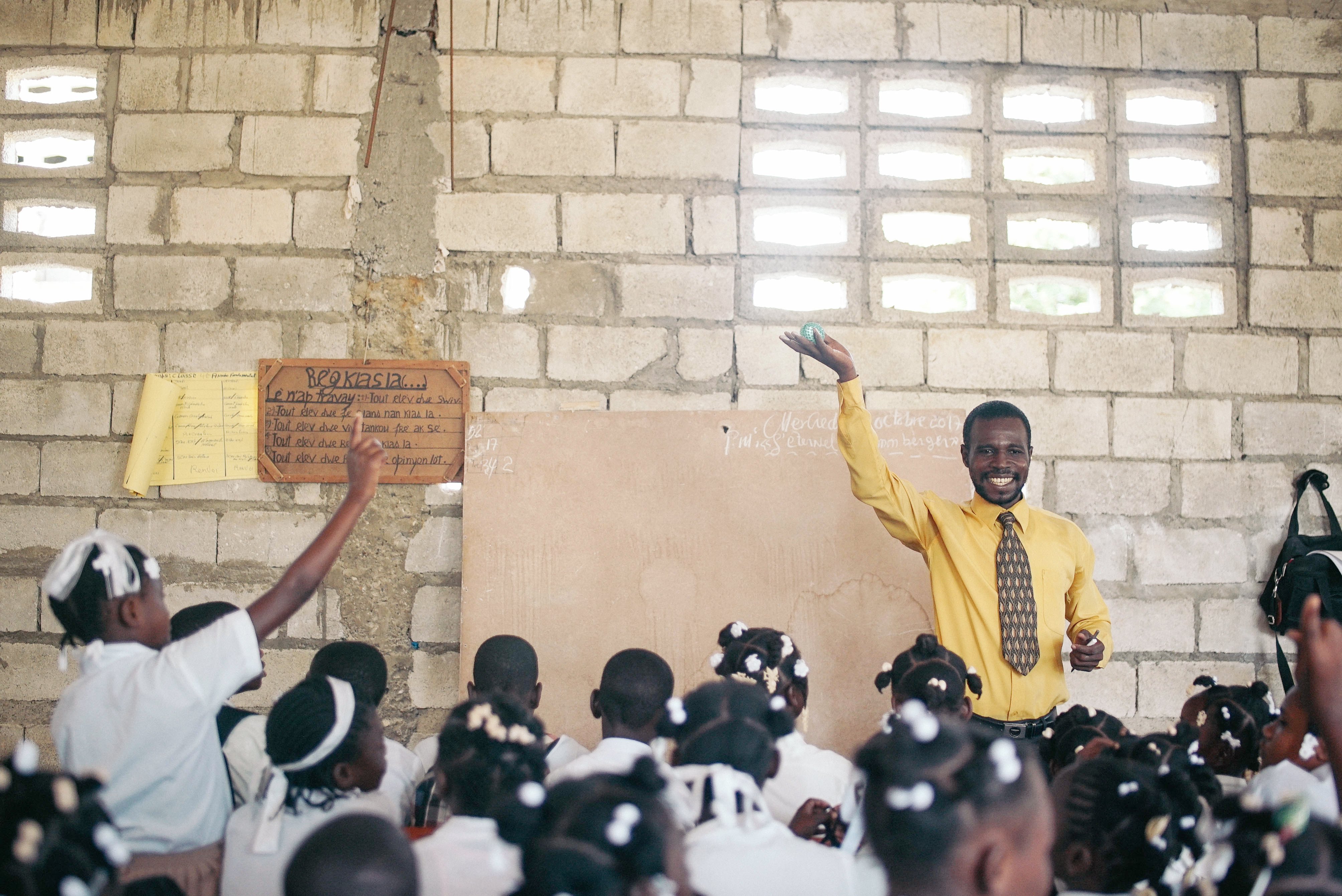 A student raises her hand in a classroom in Haiti.