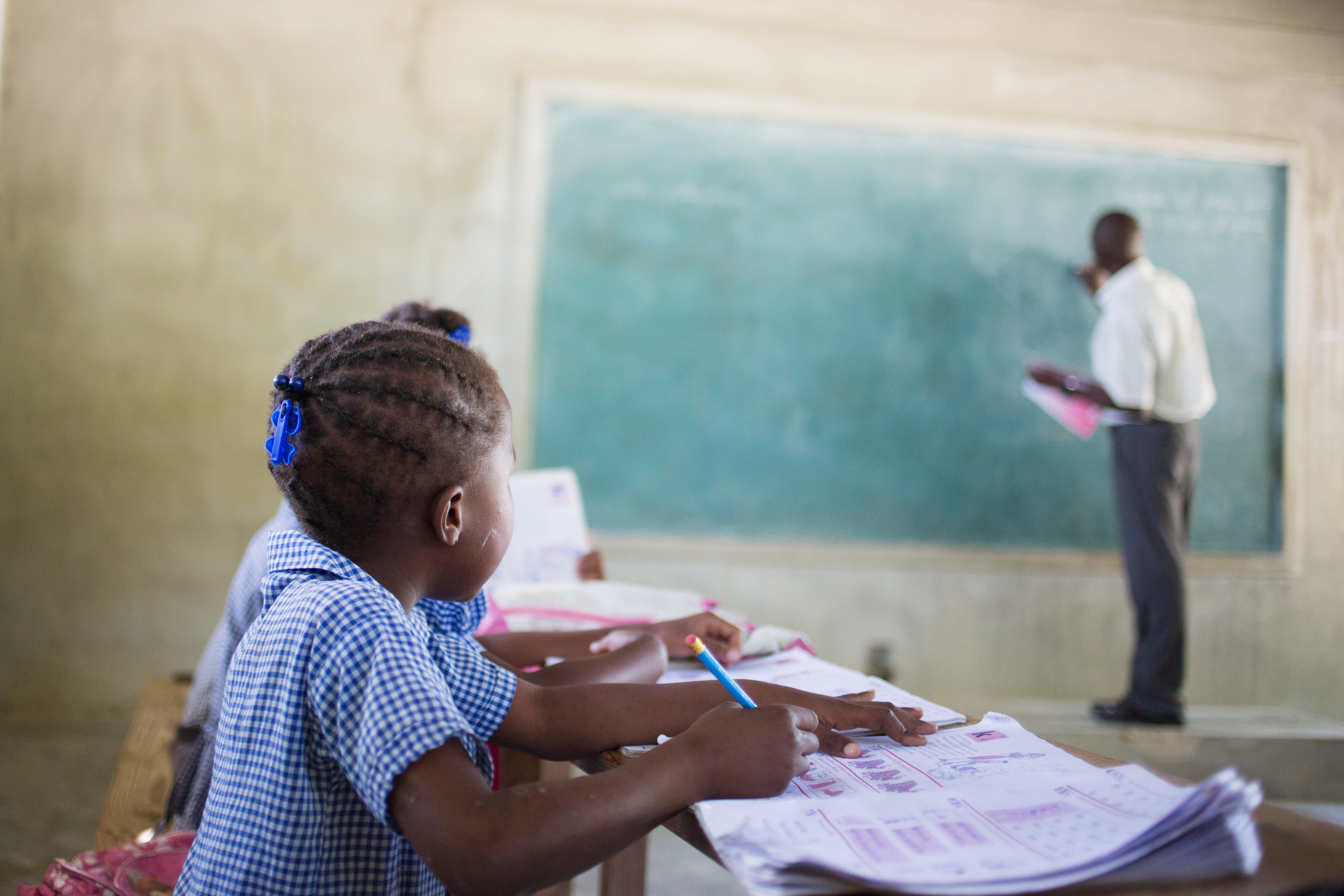 A student in Haiti looking at at the chalkboard.
