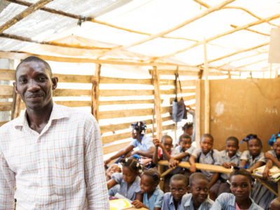 A teacher in Haiti poses with his classroom in the background.