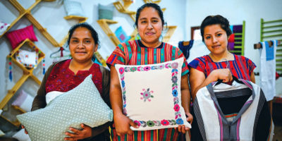 Three Indigenous women in Chiapas, Mexico, holding textile goods such as pillows and shirts.