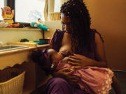 Victoria Washington holds her daughter on her lap to breastfeed.