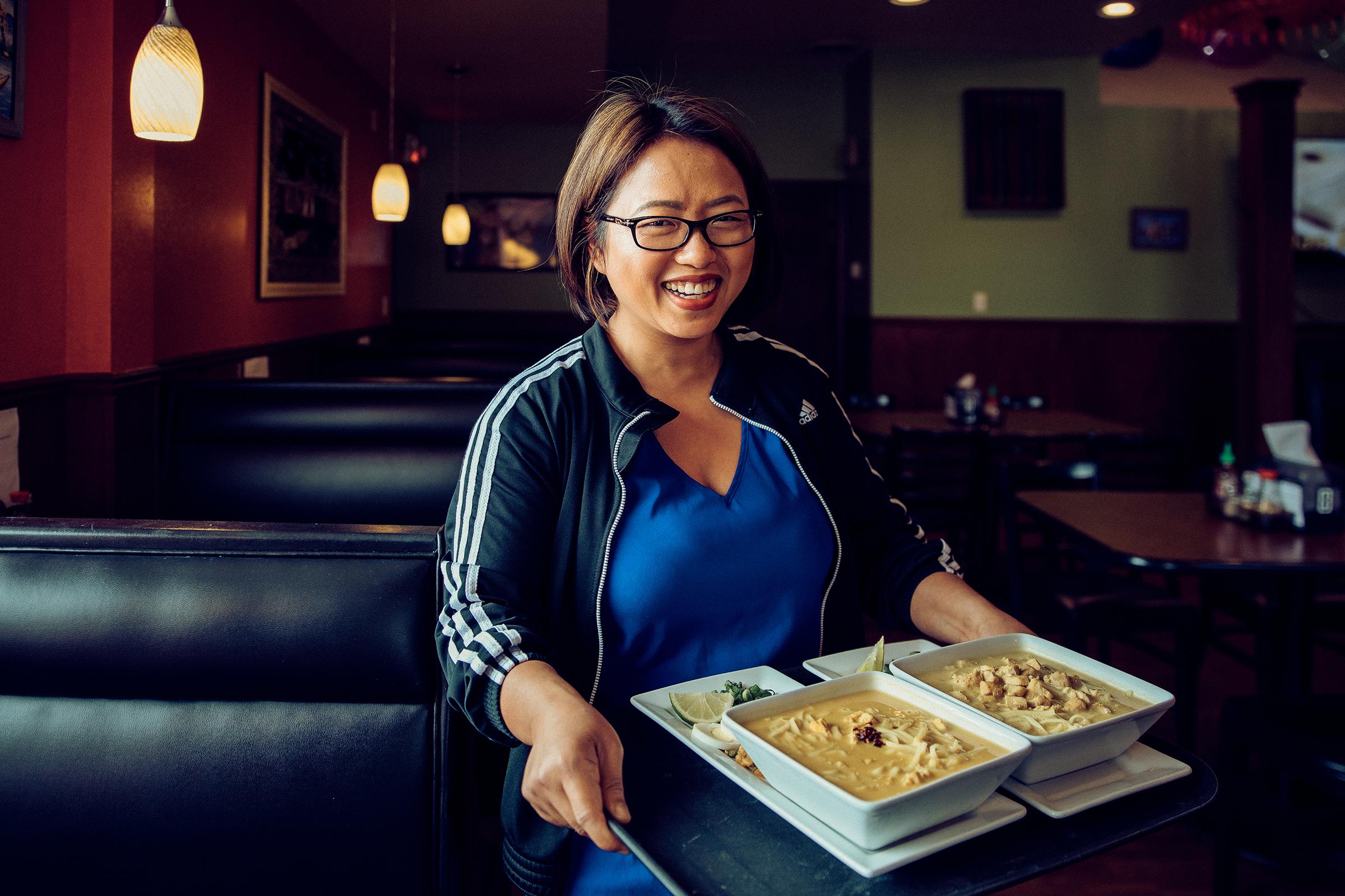 Amanda Sunthang carrying a tray of food inside the Shwe Mandalay Burmese Cuisine restaurant in Battle Creek, Michigan.