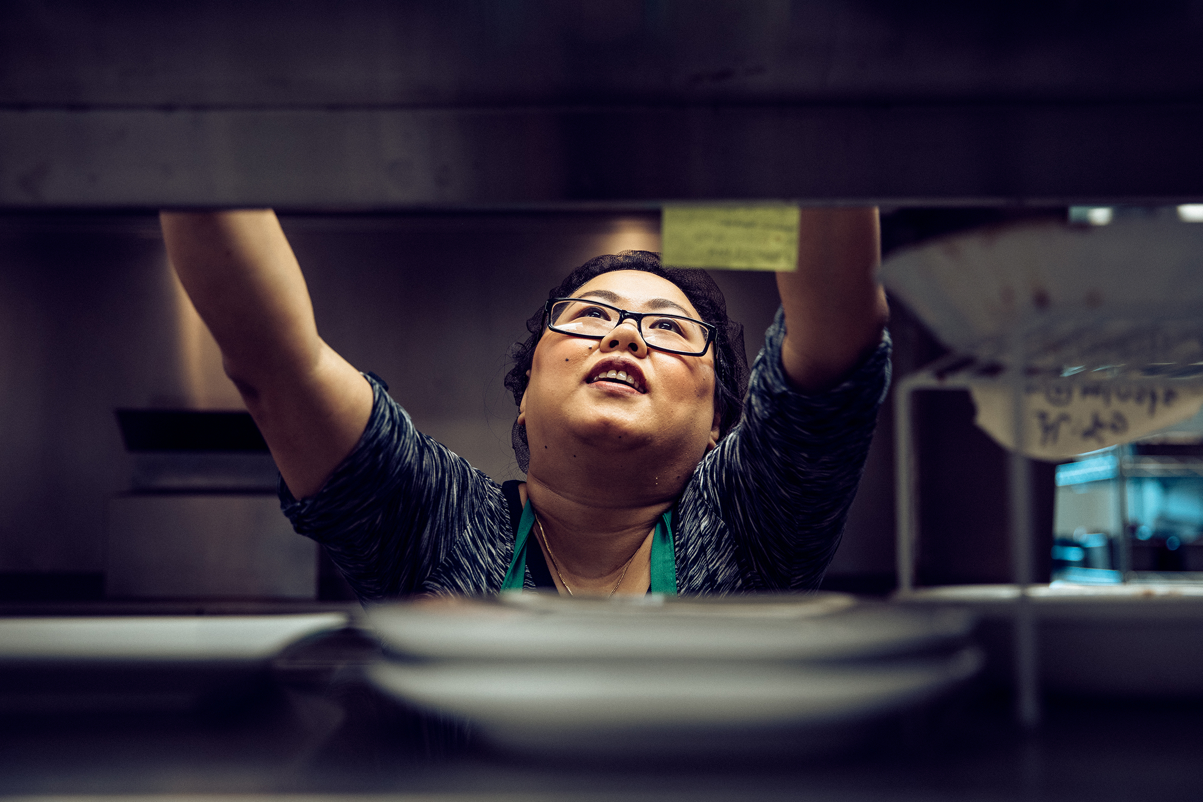 A woman reaching to grab an ingredient on the top shelf in the kitchen at the Shwe Mandalay Burmese Cuisine restaurant in Battle Creek, Michigan.