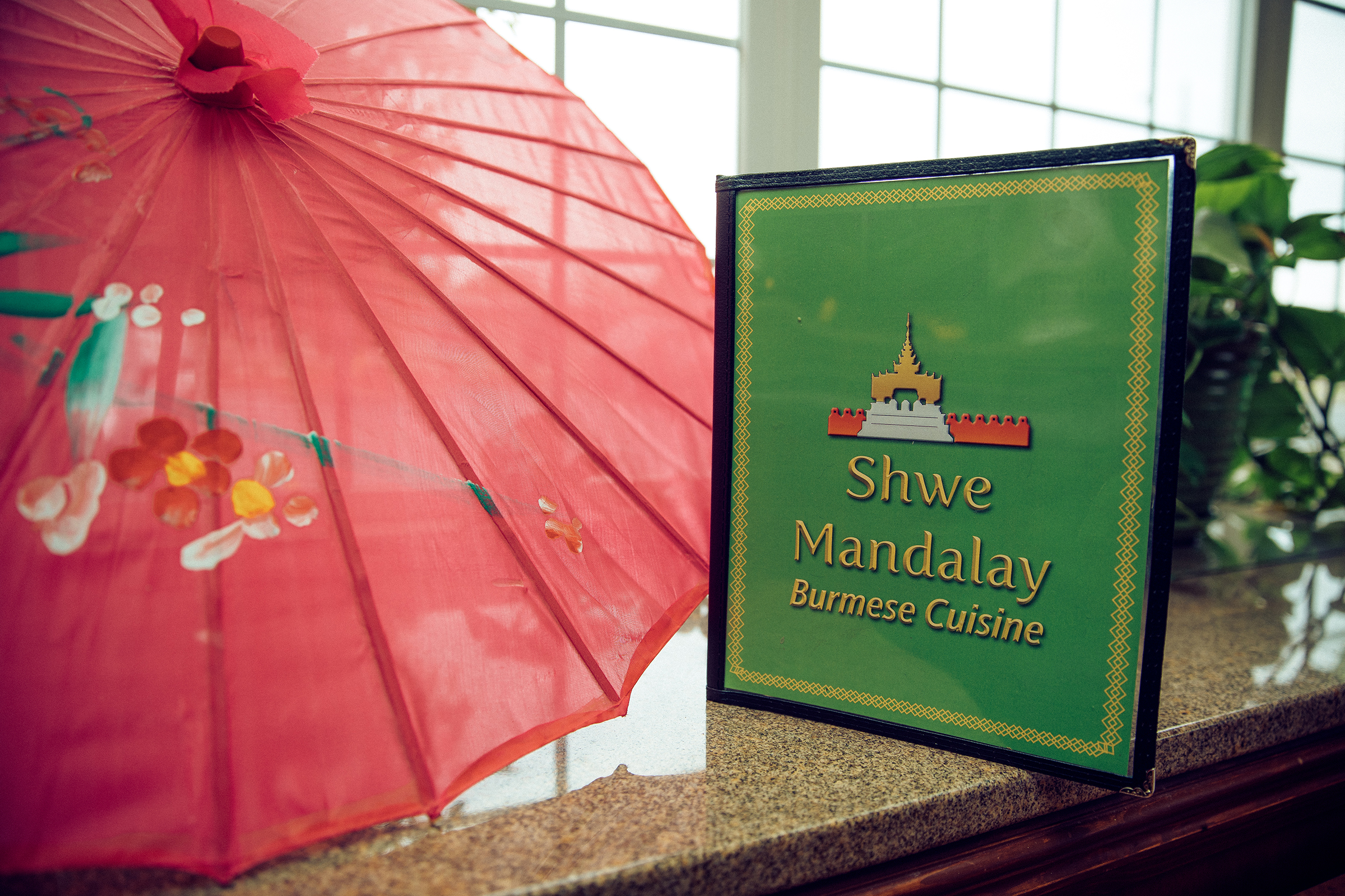 The Shwe Mandalay Burmese Cuisine restaurant menu next to a red traditional Asian umbrella in Battle Creek, Michigan.
