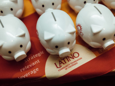 White colored piggy banks on a table with the logo and text of the nonprofit, Latino Community Foundation of Colorado.