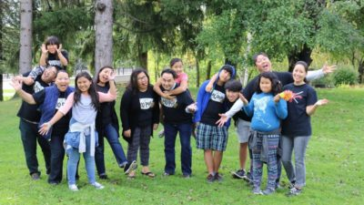 A group of Hmong Americans from the Bad Mo Pho Phamily (BMPP) Giving Circle outside.