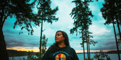 Potlatch Fund's former Development and Communications Manager Damara Jacobs-Morris looking off to the left with the backdrop of trees and sea behind her.