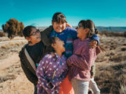 Four students looking at each other and laughing outside at the Keres Children's Learning Center in New Mexico.