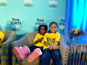 Two young children wearing yellow tshirts sitting on a chair at the Hope Starts Here Summit in Detroit.
