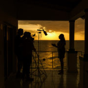 Behind the scenes with an interviewee with the sun setting in the background in Haiti.