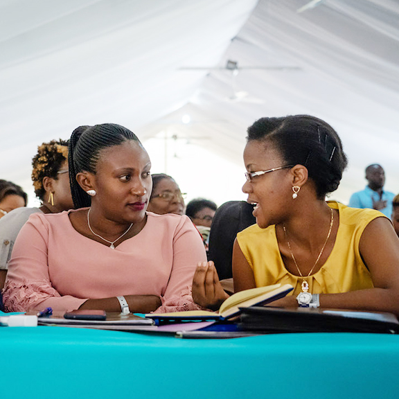 Gisèle Umuhumuza talking with another woman at the 2019 Forum of Haitian Women Elected Officials.
