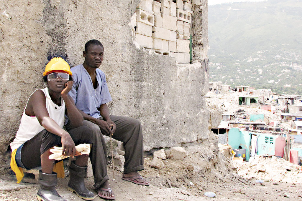 A Haitian man and woman sits among the rubble of the aftermath of the 2010 Haiti earthquake.