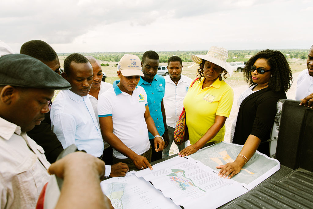 A group of Haitians discussing the the construction of new buildings in Haiti.