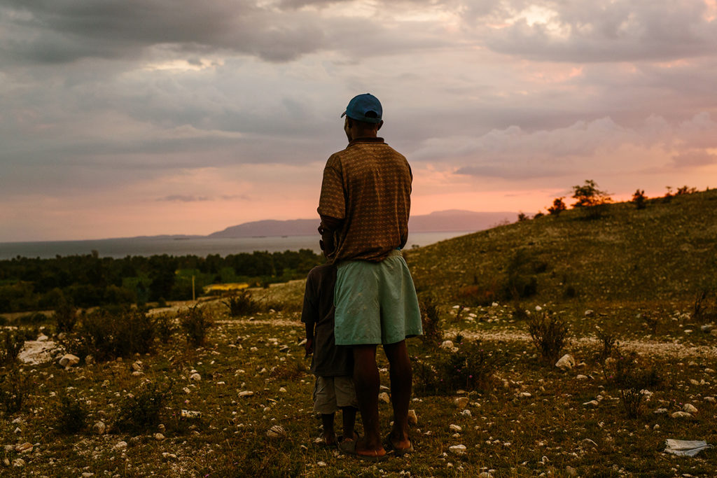 A father and son looking at the sun setting over Haiti.