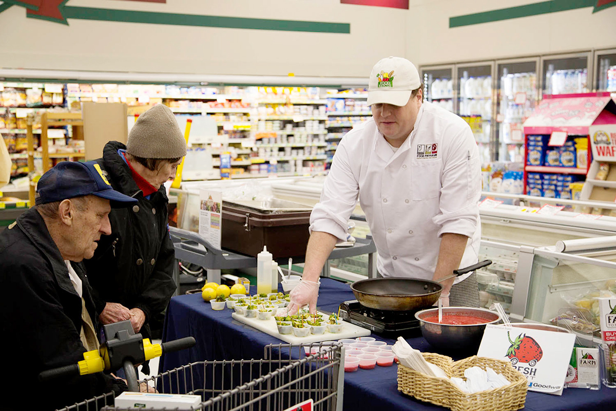 "Goodwill's ""Chef"" Ben serves up tastings at the local grocer using Goodwill's Farm to Freezer products. Photo: Farm to Freezer."