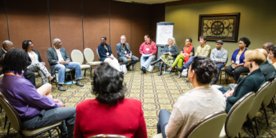 A group of diverse adults sitting in a circle and discussing racial equity.