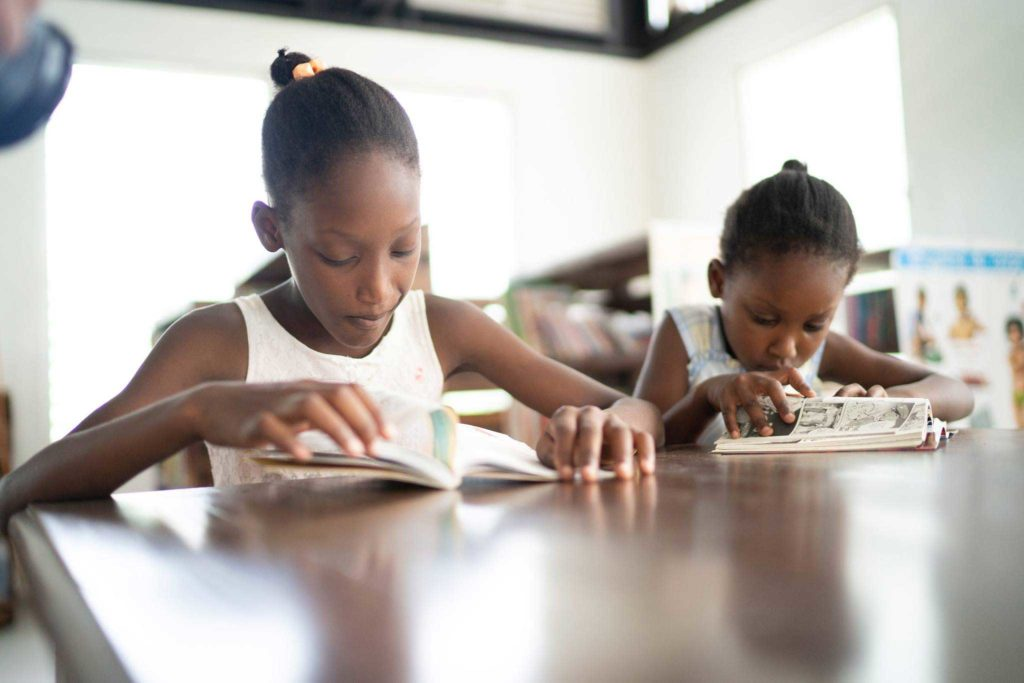 Two Haitian girls reading in Haiti Projects' Community Library