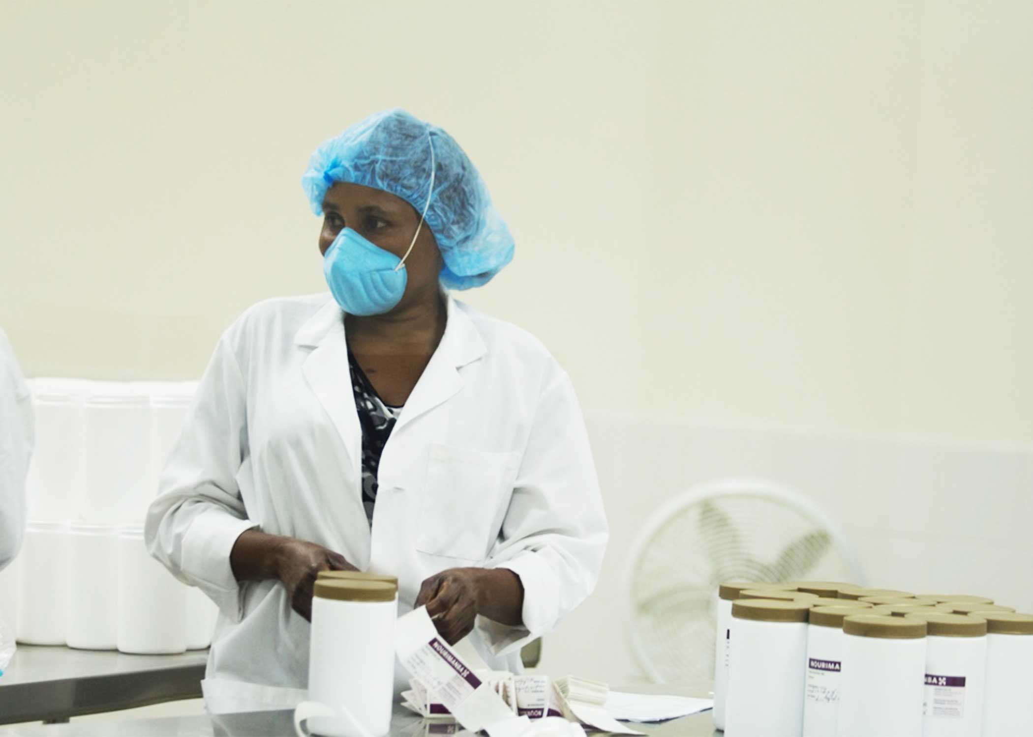 A Haitian worker in the food lab putting labels on jars of Nourimanba, the peanut-based nutritional supplement.