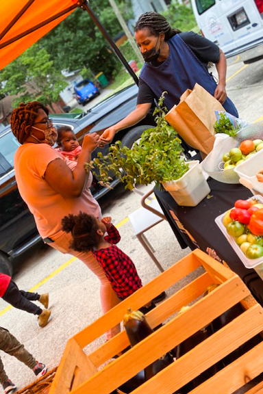A mother and her children stop by at the Little Lions Farm Stand to purchase fresh produce to bring home for the family. Photo courtesy of Little Ones Learning Center in Forest Park, GA.