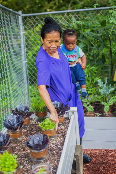 An early care and education provider showing a curious infant a small lettuce garden at Lina Lane's Learning Center in Ellenwood, GA. Photo courtesy of Quality Care for Children.